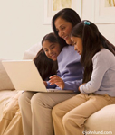 An ethnic family using thier laptop computer. Mother and two children indoors on sofa. Quality family time for a black mother and her two young children.